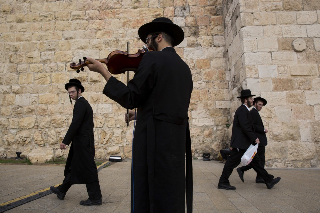 In this Wednesday, Dec. 20, 2017 photo, An ultra-Orthodox Jewish man plays his Violin during the Jewish holiday of Hanukkah, at Jaffa Gate in Jerusale...