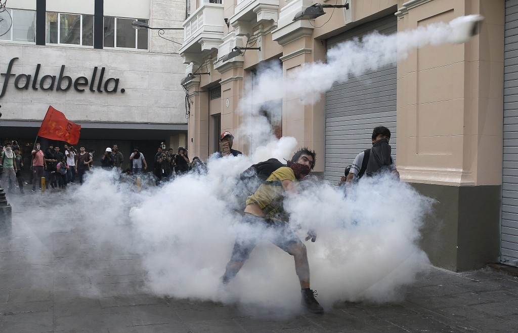 In this Dec. 25, 2017 photo, a demonstrators throws a tear gas canister back towards the police during clashes against the pardon of former President ...