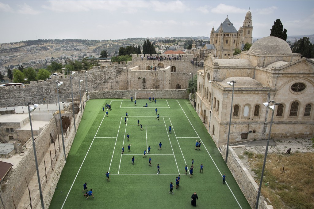 In this Friday, May 19, 2017 photo, Armenian school kids play in the soccer field located next to Jerusalem's Old City Walls at the Sts. Tarkmanchatz ...