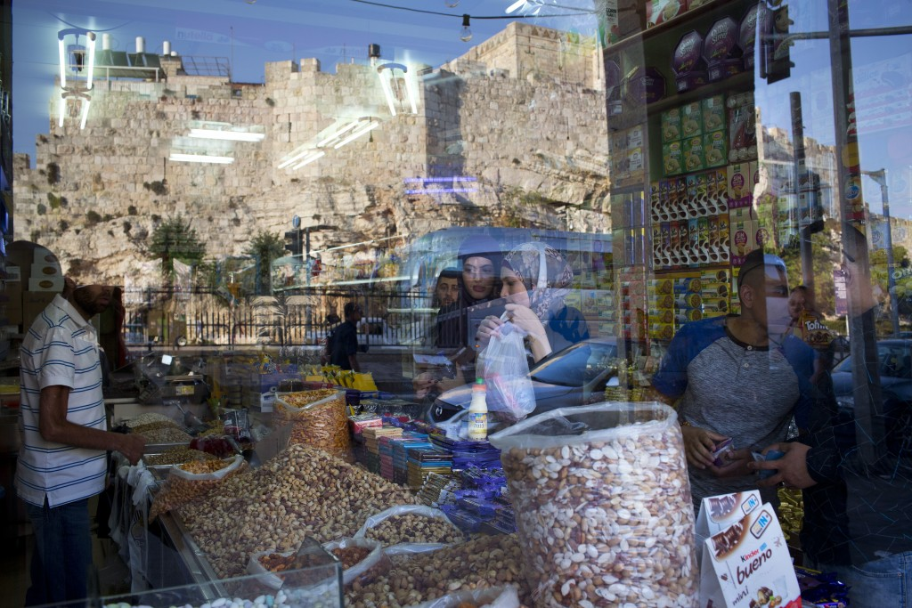 In this Saturday, Sept. 2, 2017 photo, people buy from a grocery store located between Damascus Gate and the Flowers Gate in Jerusalem's Old City. Jer...
