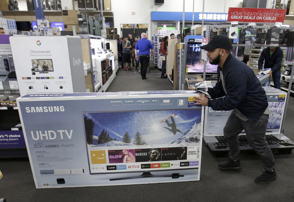 FILE - In this Nov. 23, 2017, file photo, Jesus Reyes pushes a television down an aisle as he shops at a Best Buy store in Overland Park, Kan. Just be...