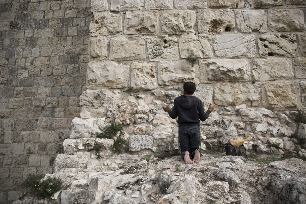 In this Tuesday, Dec. 19, 2017 photo, a man prays facing Jerusalem's Old City walls between Jaffa Gate and Zion Gate. Jerusalem's iconic Old City wall...