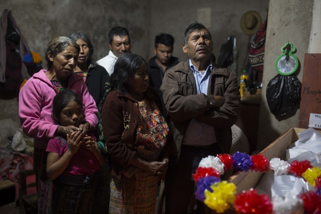 In this Nov. 29, 2017, Baltazar Perez Sanchez, 71, mourns next to the coffin of his mother Magdalena, who died at age 65, during her wake in Santa Ave...