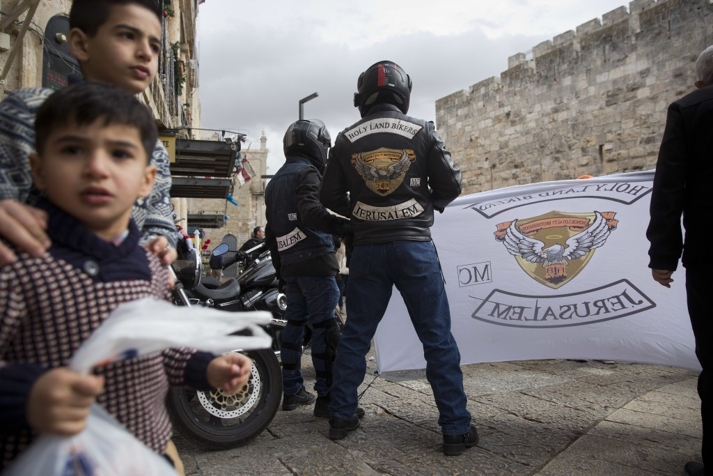 In this Sunday, Dec. 24, 2017 photo, Members of Holy Land Bikers group gather in Jerusalem Old City before riding their motorbikes to Bethlehem on Chr...