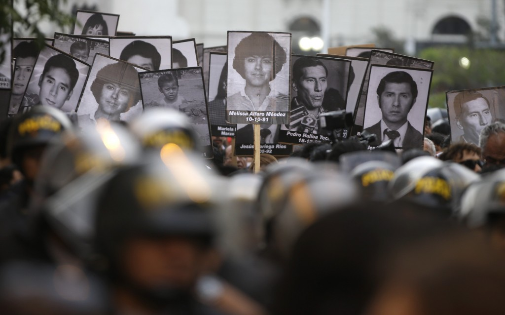 Demonstrators march during a protest against the pardon of former President Alberto Fujimori holding photographs of people who disappeared during his ...