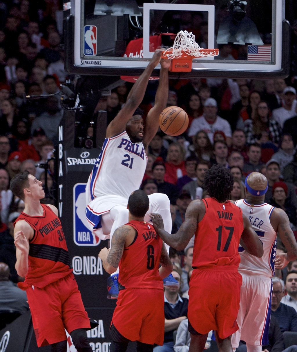 Philadelphia 76ers center Joel Embiid, center, dunks against the Portland Trail Blazers during the first half of an NBA basketball game in Portland, O...