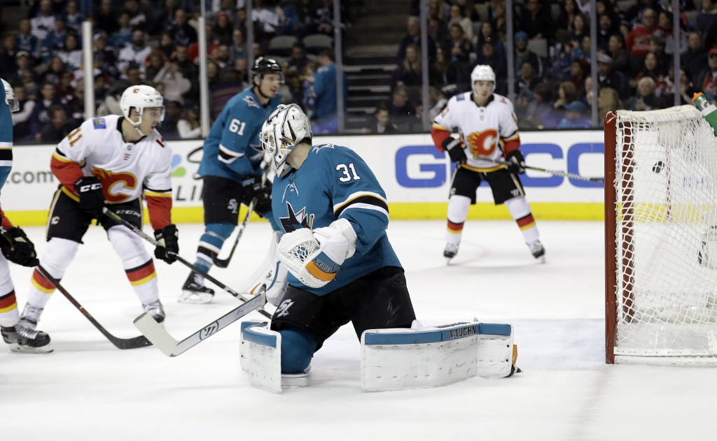 San Jose Sharks goalie Martin Jones (31) is beaten for a goal on a shot from Calgary Flames' Mikael Backlund, not seen, during the first period of an ...