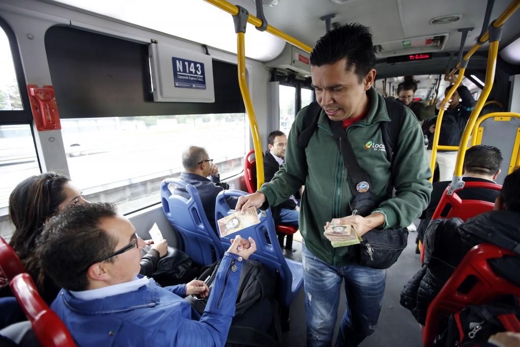 In this Dec. 12, 2017 photo, Venezuelan national Jorge Gutierrez hands a 100 bolivar Venezuelan bill to a passenger, as he attempts to sell his Venezu...