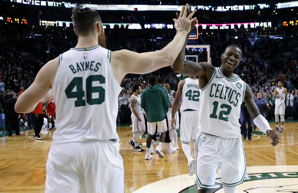 Boston Celtics' Terry Rozier (12) and Marcus Smart (36) celebrate after defeating the Houston Rockets in an NBA basketball game in Boston, Thursday, D...
