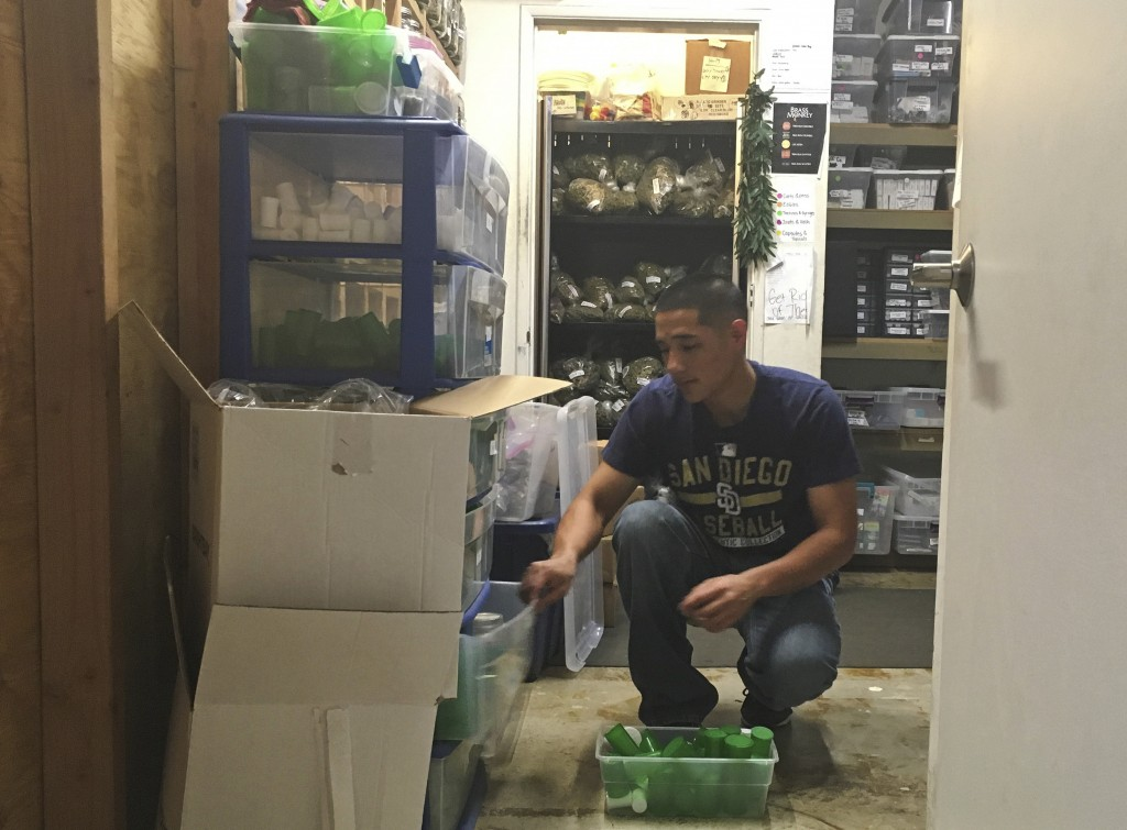 In this Dec. 27, 2017 photo, Golden State Greens employee Alex Bradley loads product in the inventory room at the back office in San Diego, Calif. Doz...