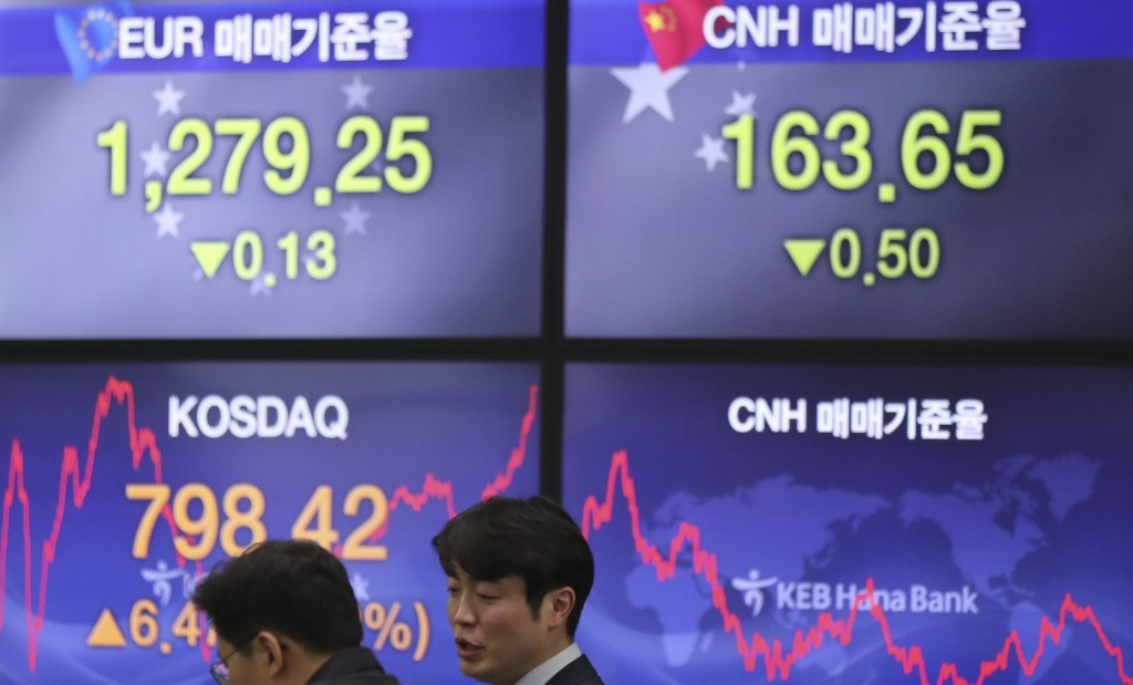 Currency traders talk near the screens showing the foreign exchange rates at the foreign exchange dealing room in Seoul, South Korea, Friday, Dec. 29,...