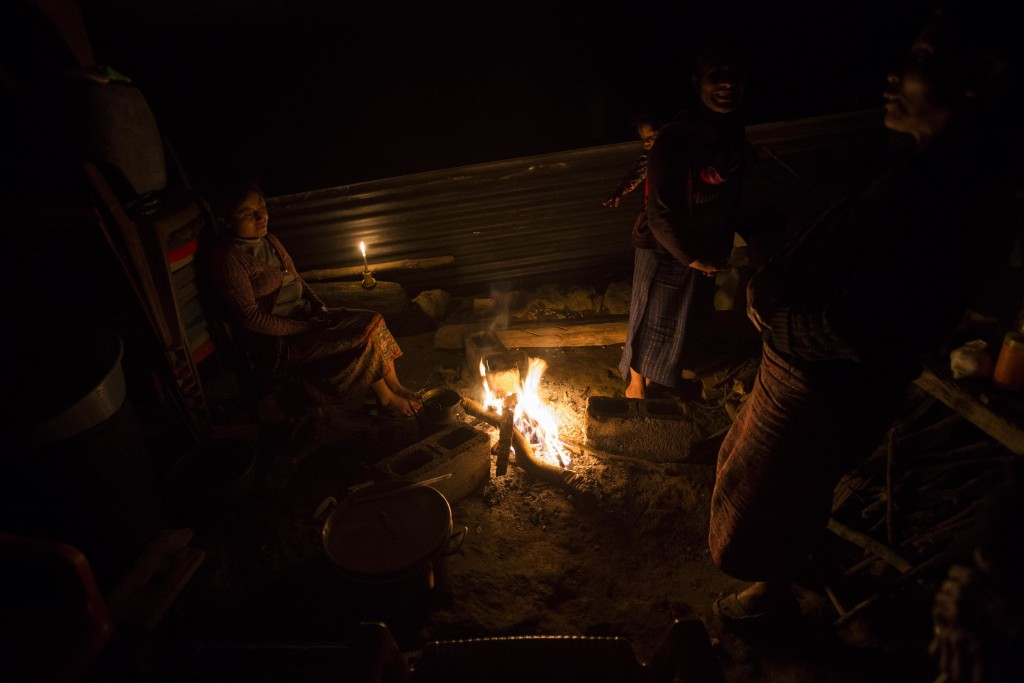 In this Nov. 29, 2017 photo, the relatives of civil war victim Antonio Perez Velasco, whose remains were exhumed and identified, sit around a campfire...