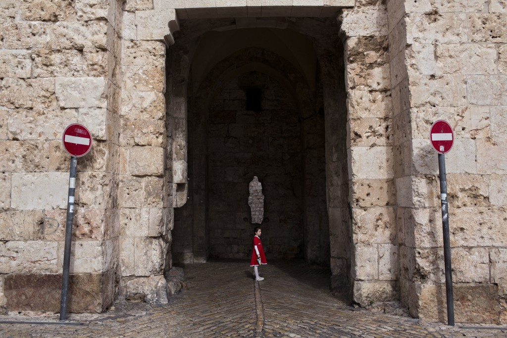In this Tuesday, Dec. 19, 2017 photo, a young girl waits for her family to cross the Zion Gate in Jerusalem Old City. Jerusalem's iconic Old City wall...