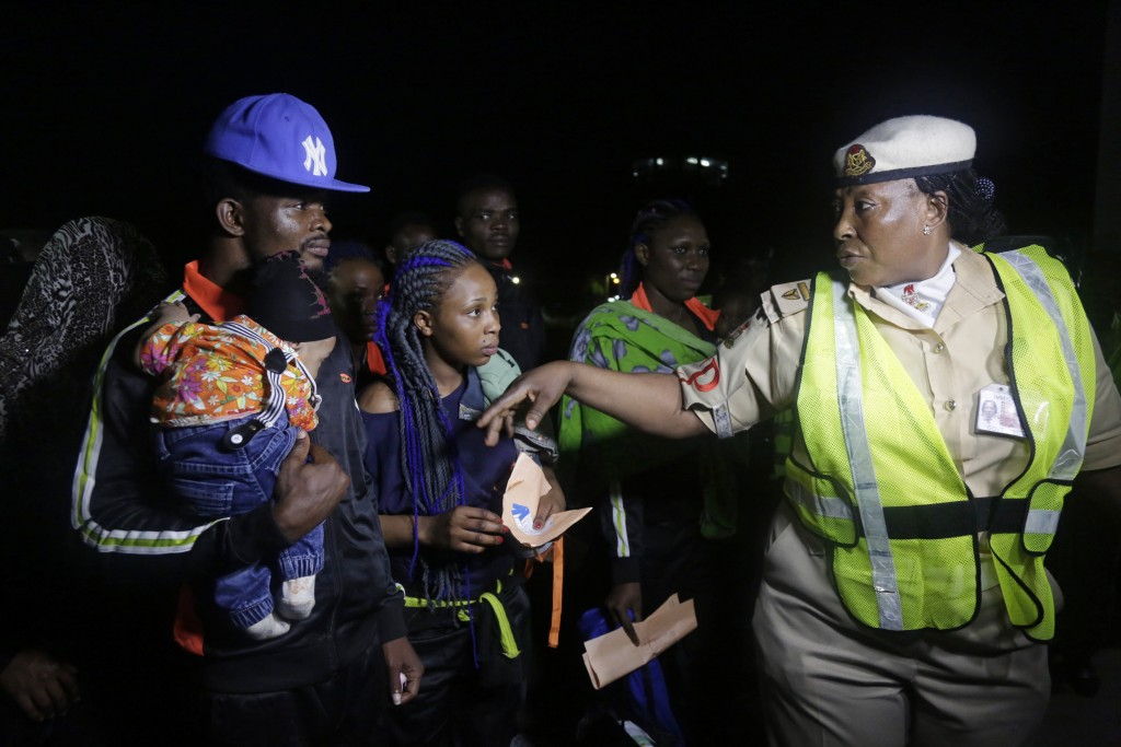 FILE - In this Dec. 5, 2017, file photo, an unidentified immigration officer, right, speaks to Nigerian returnees from Libya upon arrival at the Murta...