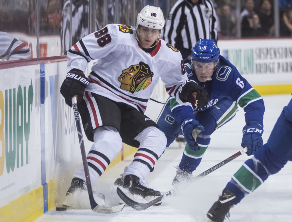 Chicago Blackhawks' Patrick Kane, left, and Vancouver Canucks' Brock Boeser vie for the puck during the first period of an NHL hockey game Thursday, D...