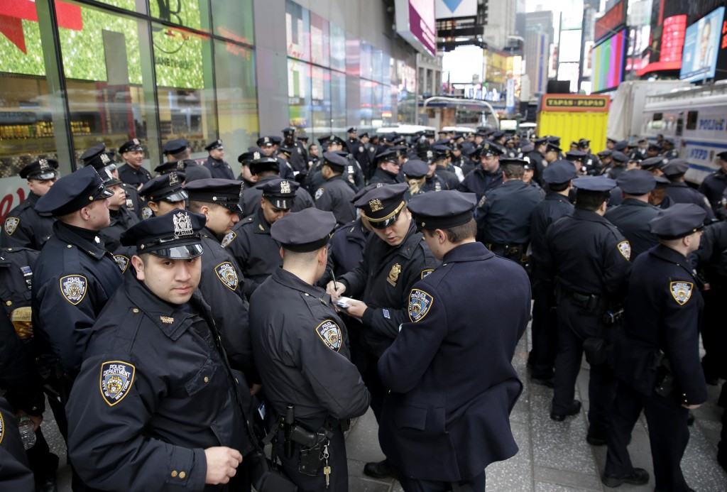FILE- In this Dec. 31, 2015 file photo, police officers gather at the southern end of Times Square to receive their assignments for New Year's Eve in ...