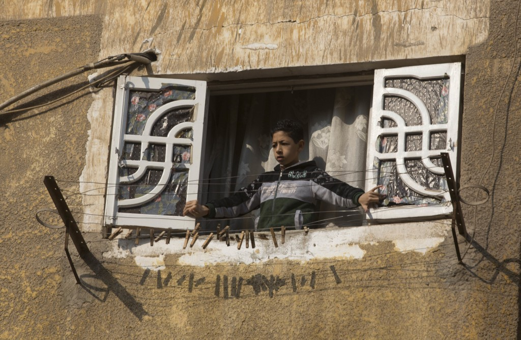 A boy watches the site of Mar Mina church, in Helwan, Cairo, Egypt, Friday, Dec. 29, 2017, where several people have been killed in a shootout outside...