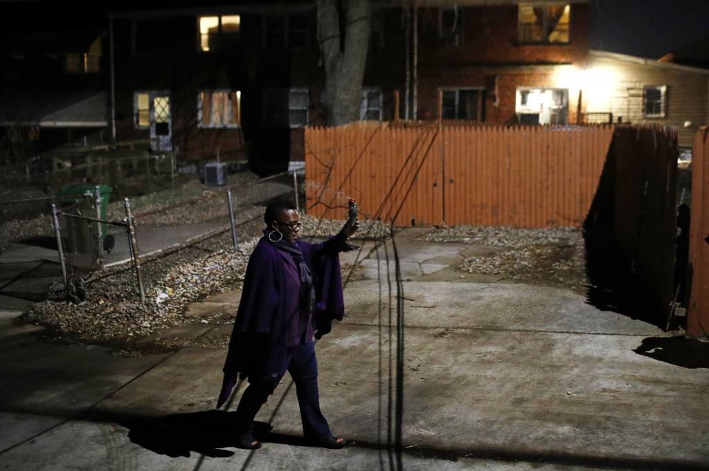 In this Dec. 11, 2017 photo, Erricka Bridgeford carries burning sage as she performs a ceremony in a back alley near the scene of a homicide in Baltim...