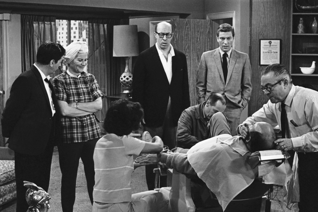 FILE- In this April 11, 1963, file photo, standing from left, Morey Amsterdam, Rose Marie, and Richard Deacon, and Dick Van Dyke, right, gather around...