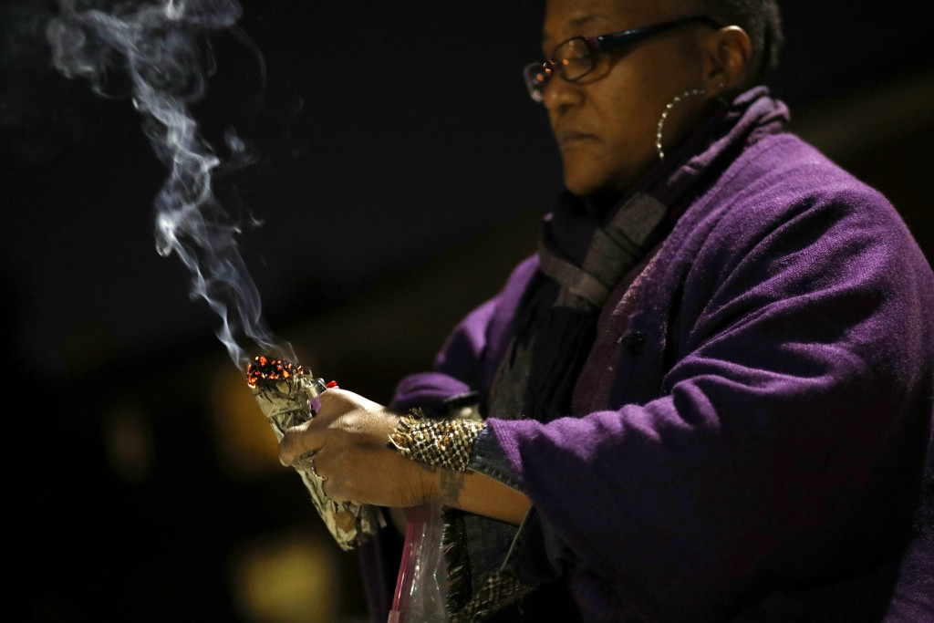 In this Dec. 11, 2017 photo, Erricka Bridgeford burns sage as she performs a ceremony near the scene of a homicide in Baltimore. Bridgeford lost a bro...
