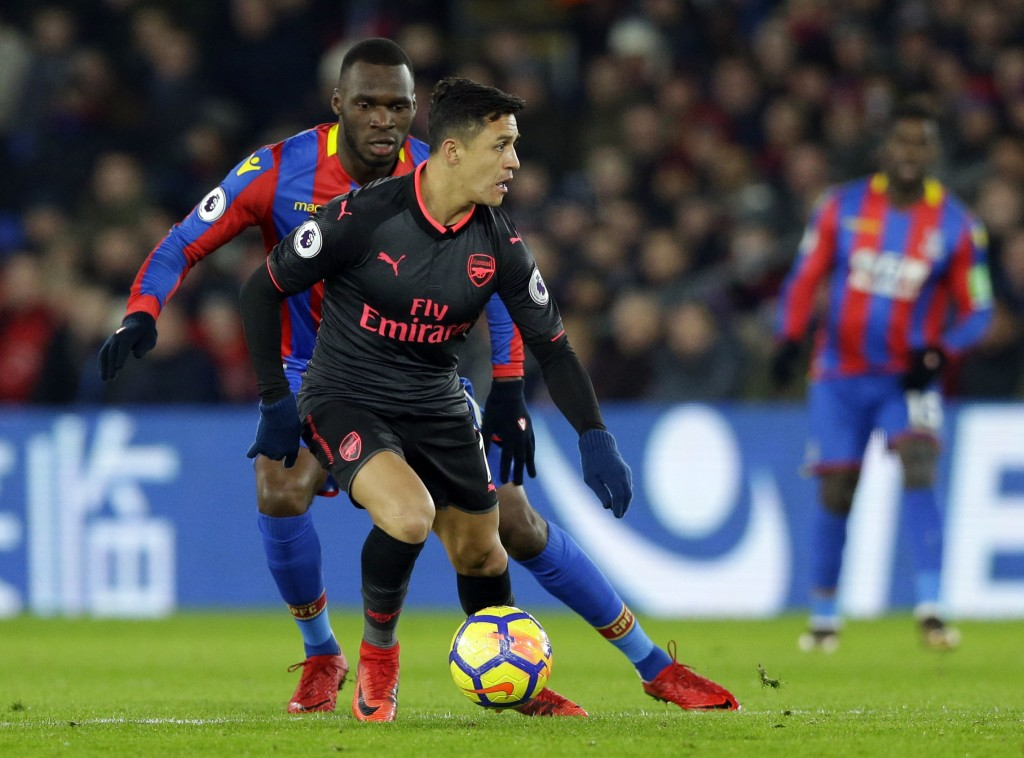 Arsenal's Alexis Sanchez, front, shields the ball from Crystal Palace's Christian Benteke during their English Premier League soccer match between Cry...