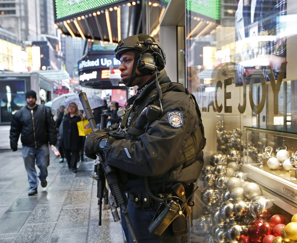 FILE - In this Dec. 29, 2016 file photo, a heavily armed counterterrorism officer takes shelter beneath an overhang above a store in Times Square in N...