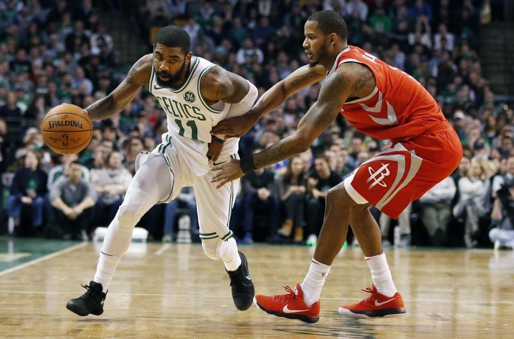 Boston Celtics' Kyrie Irving (11) drives past Houston Rockets' Trevor Ariza during the second quarter of an NBA basketball game in Boston, Thursday, D...