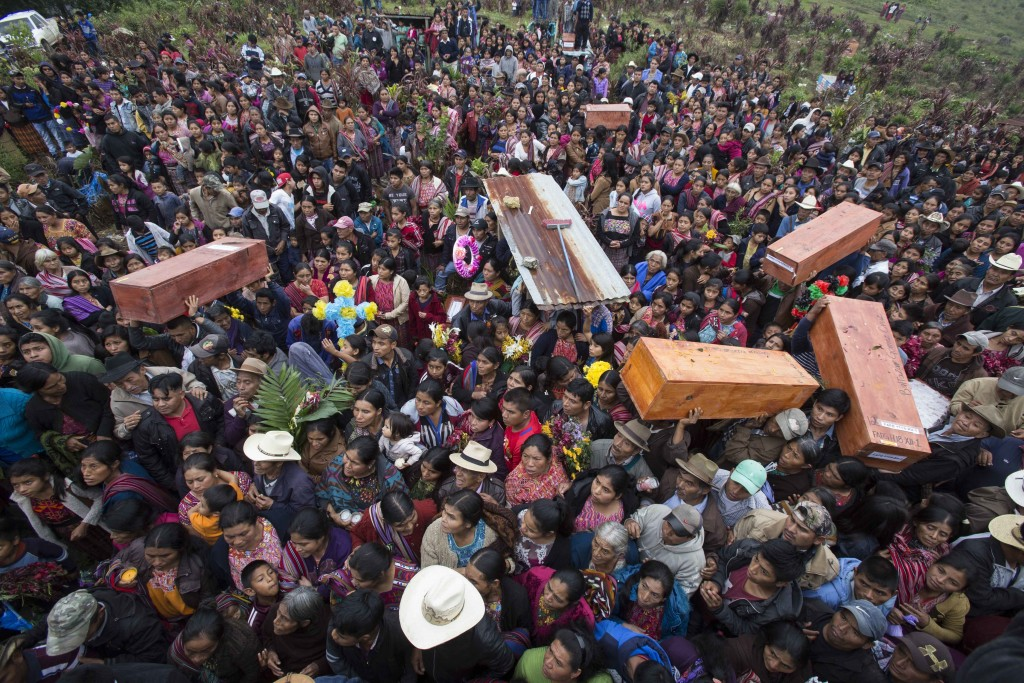 In this Nov. 30, 2017 photo, locals carry the remains of family members who were killed during the civil war,  to finally be buried in Santa Avelina, ...