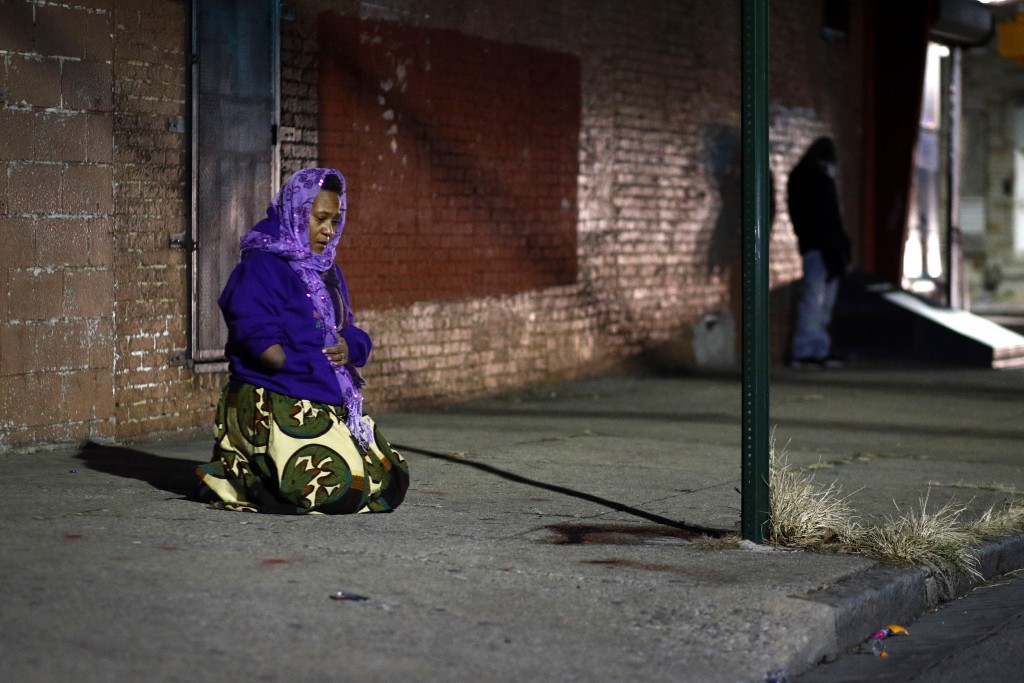 In this Dec. 14, 2017 photo, Erricka Bridgeford kneels as she performs a ceremony in front of blood stains that were left behind at a homicide scene i...