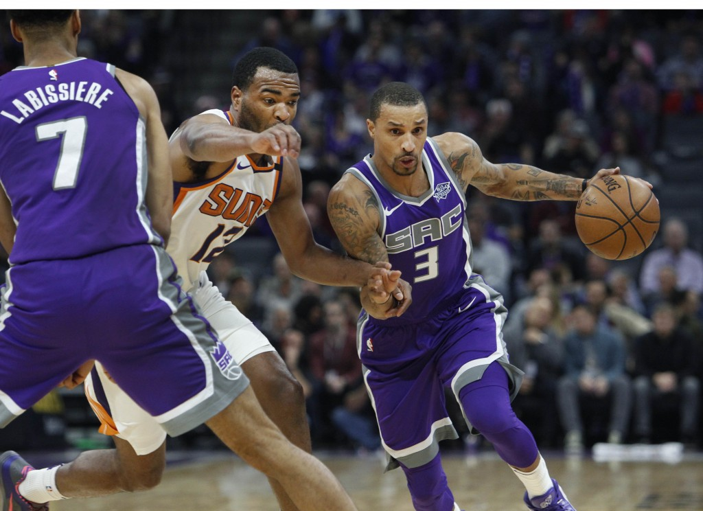 Sacramento Kings guard George Hill (3) drives to the basket around Phoenix Suns forward TJ Warren (12) during the first half of an NBA basketball game...