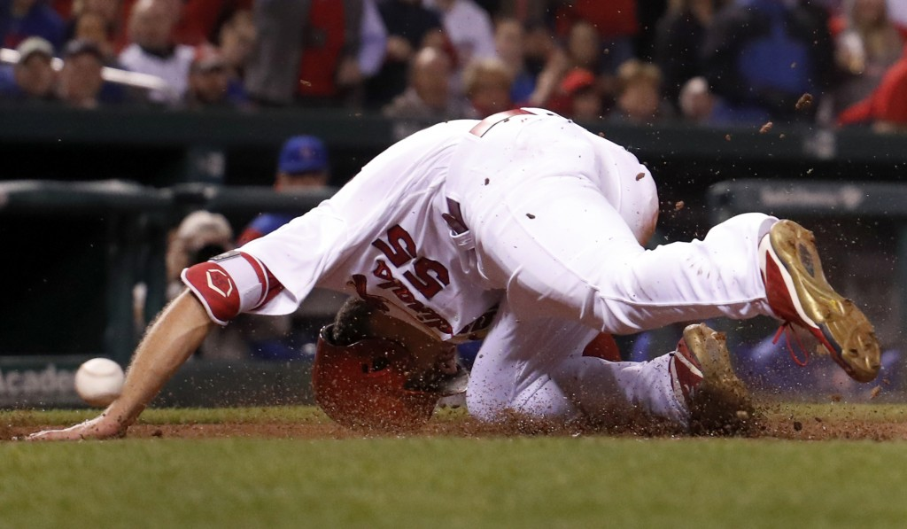 FILE - In this April 4, 2107, file photo, St. Louis Cardinals' Stephen Piscotty falls after being hit on the head with the ball while scoring during t...