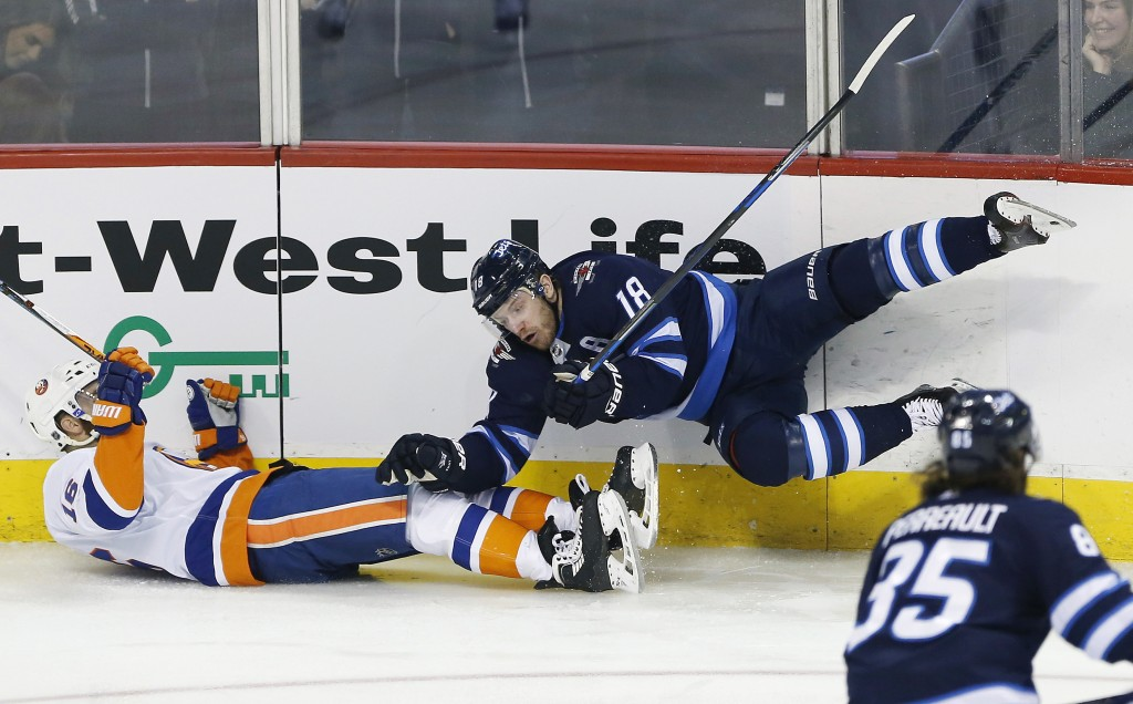 Winnipeg Jets' Bryan Little (18) and New York Islanders' Andrew Ladd (16) collide during first-period NHL hockey game action in Winnipeg, Manitoba, Fr...