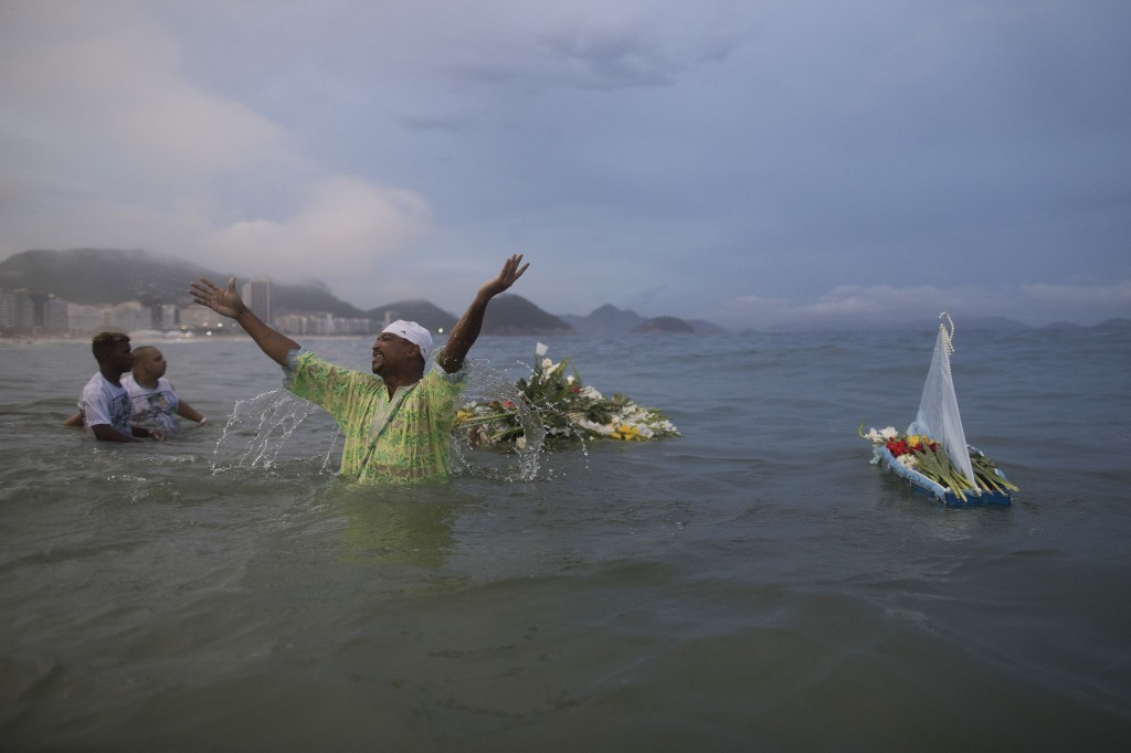 A faithful gestures after carrying a boat into the water filled with offerings for Yemanja, goddess of the sea, during a ceremony that is part of trad...