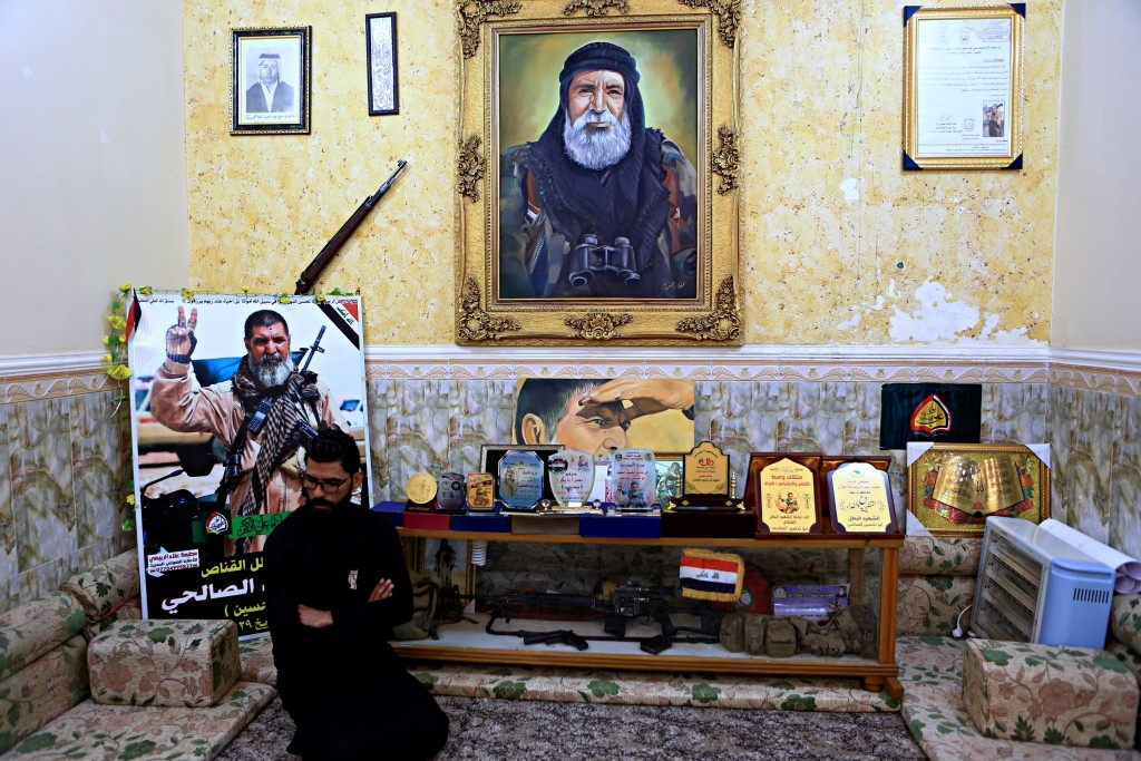 In this Tuesday, Dec. 5, 2017 photo, a man sits among awards, certificates of appreciation and posters belonging to the sniper Ali Jayad al-Salhi, 65,...