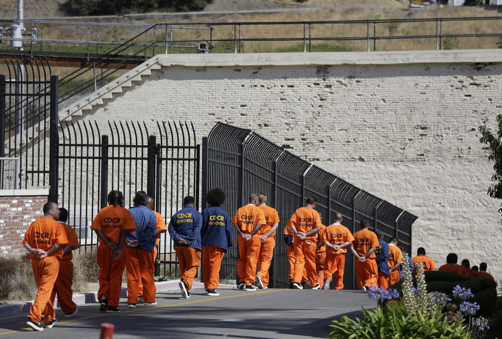 In this Aug. 16, 2016 photo, a row of general population inmates walk in a line at San Quentin State Prison in San Quentin, Calif. California state la...