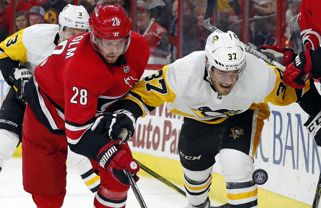 Carolina Hurricanes' Elias Lindholm (28) and Pittsburgh Penguins' Carter Rowney (37) vie for the puck during the second period of an NHL hockey game F...