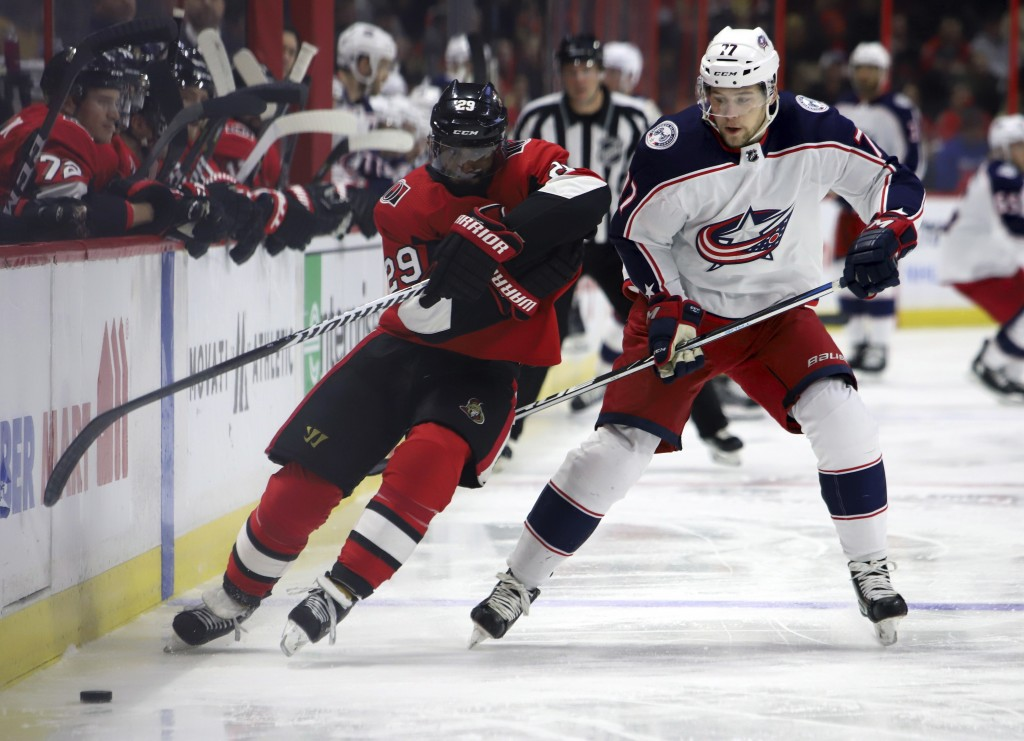 Ottawa Senators' Johnny Oduya (29) and Columbus Blue Jackets' Josh Anderson (77) race for the puck along the boards during the first period of an NHL ...