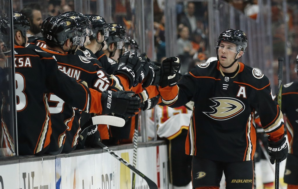 Anaheim Ducks defenseman Cam Fowler, right, celebrates scoring against the Calgary Flames with teammates on the bench during the first period of an NH...