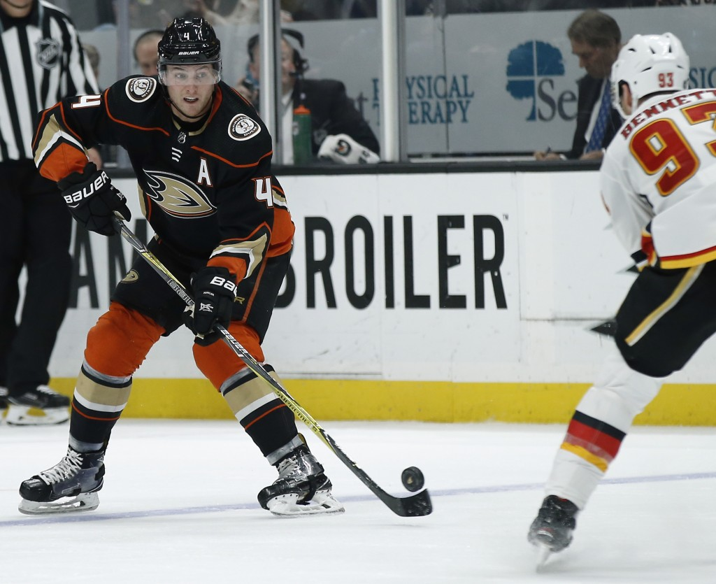 Anaheim Ducks defenseman Cam Fowler, left, passes the puck away from Calgary Flames center Sam Bennett, right, during the second period of an NHL hock...