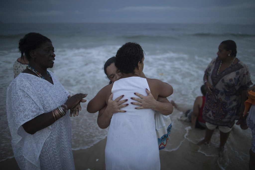 A woman in a trance hugs a faithful during a ceremony for Yemanja, goddess of the sea, that is part of traditional New Year's celebrations on Copacaba...
