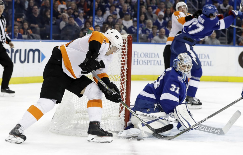 Tampa Bay Lightning goalie Peter Budaj (31), of Slovakia, makes a save as Philadelphia Flyers center Jori Lehtera (15), of Finland, tries to wrap the ...