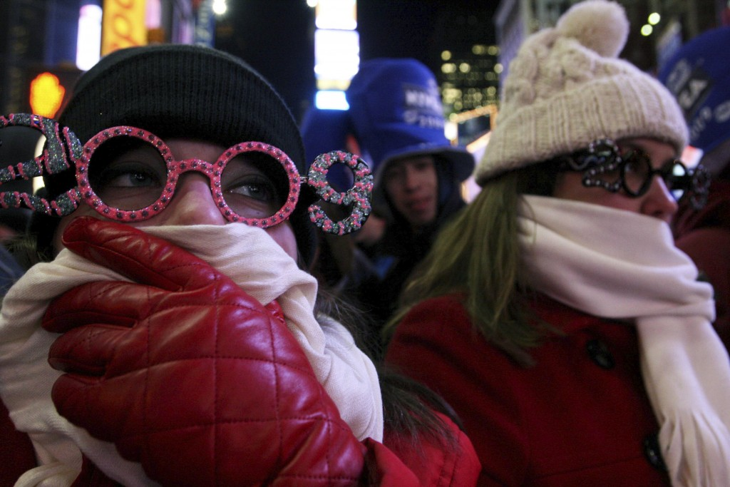 FILE- In this Dec. 31, 2008 file photo, Allison Smith of Jacksonville, Fla, left, tries to keep warm as she and others take part in the New Year's Eve