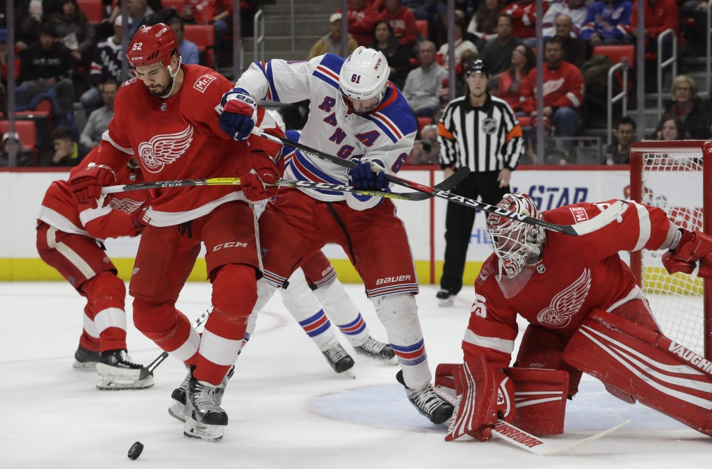 Detroit Red Wings defenseman Jonathan Ericsson (52) and New York Rangers right wing Rick Nash (61) try controlling the puck in front of Red Wings goal...