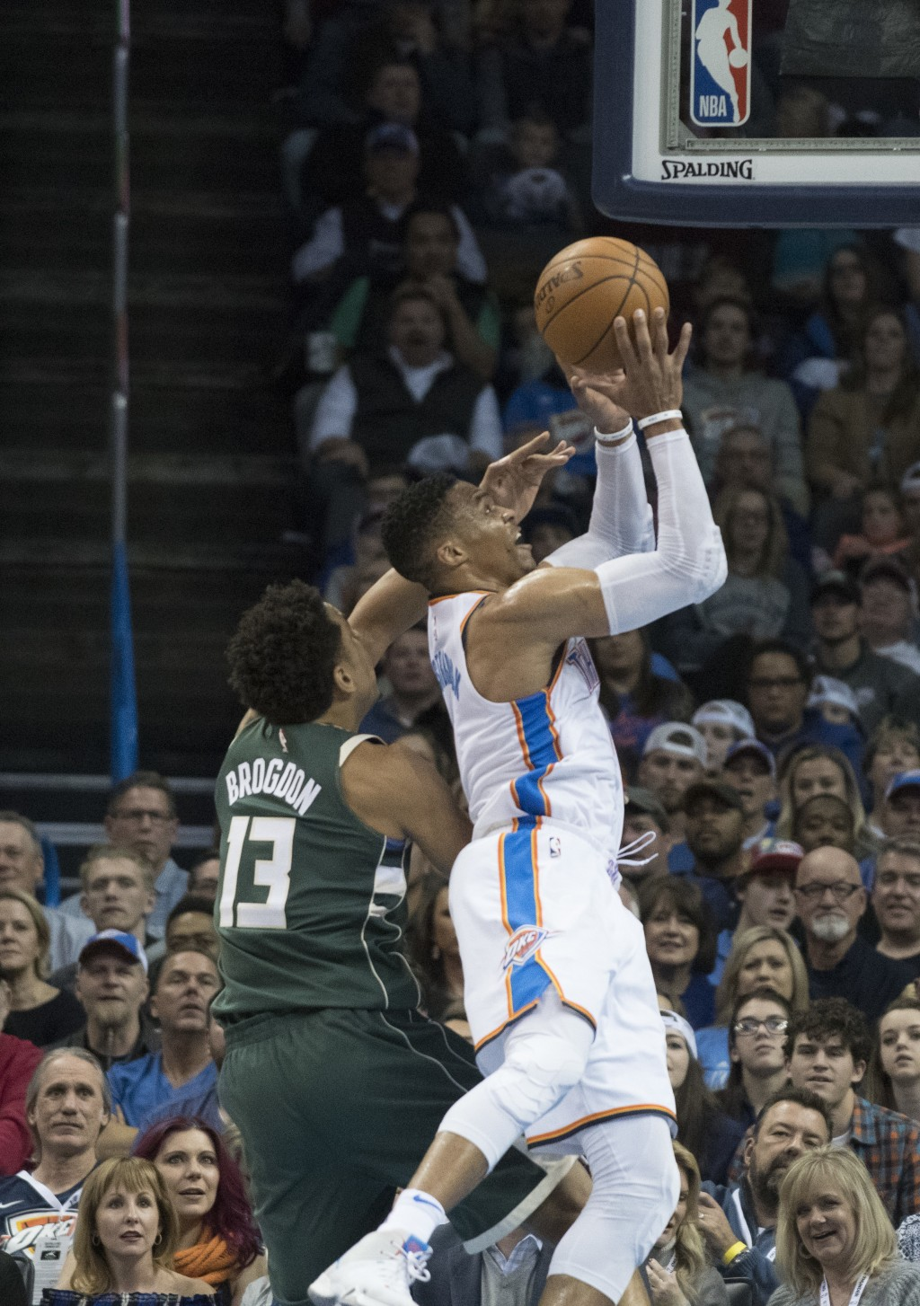 Oklahoma City Thunder guard Russell Westbrook (0) shoots two points as he slides past Milwaukee Bucks guard Malcolm Brogdon (13) during the first half...