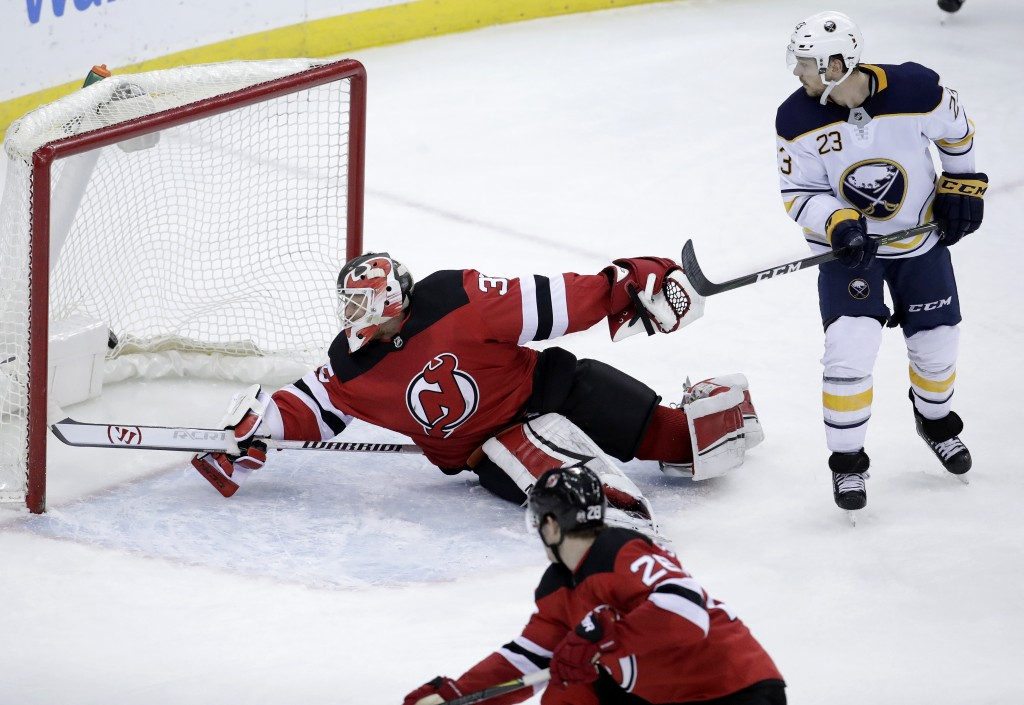 New Jersey Devils goalie Cory Schneider, center, dives but is unable to block a scoring shot by Buffalo Sabres center Jack Eichel, not pictured, durin...