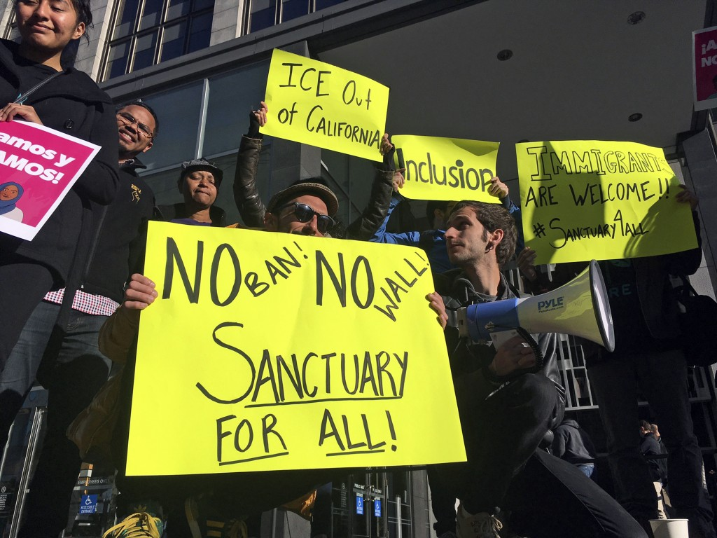 FILE - In this April 14, 2017, file photo, protesters hold up signs outside a courthouse where a federal judge was to hear arguments in the first laws...