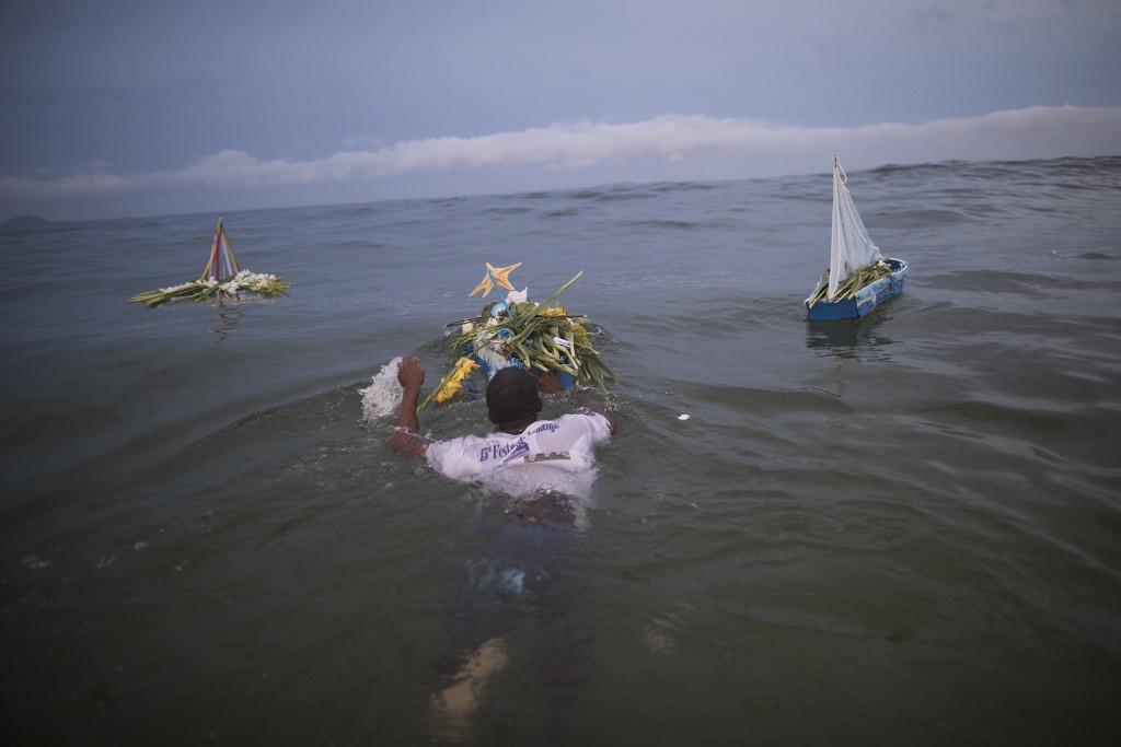 A faithful carries a boat filled with offerings for Yemanja, goddess of the sea, during a ceremony that is part of traditional New Year's celebrations...