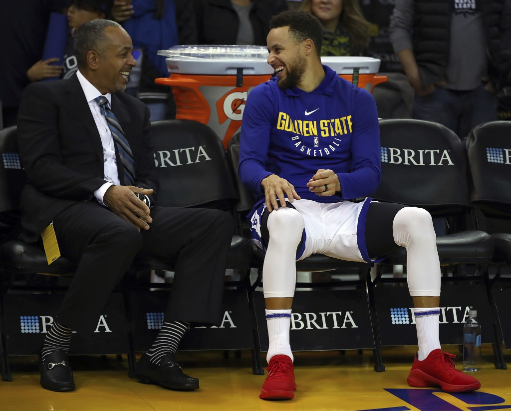 Golden State Warriors' Stephen Curry, right, laughs with his father Dell Curry prior to an NBA basketball game against the Charlotte Hornets on Friday...