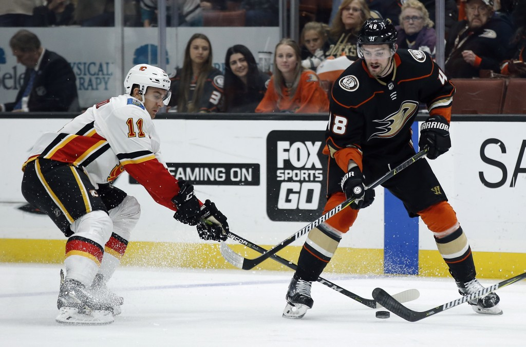 Calgary Flames center Mikael Backlund, left, of Sweden, takes the puck away from Anaheim Ducks center Logan Shaw during the second period of an NHL ho...
