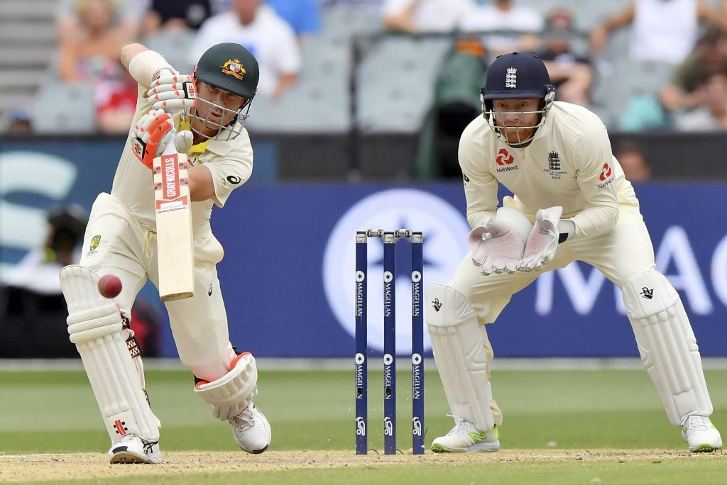 Australia's David Warner, left, drives the ball in front of England's Jonny Bairstow during the fifth day of their Ashes cricket test match in Melbour...